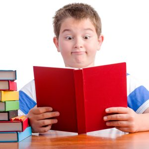 Surprised schoolboy reading book