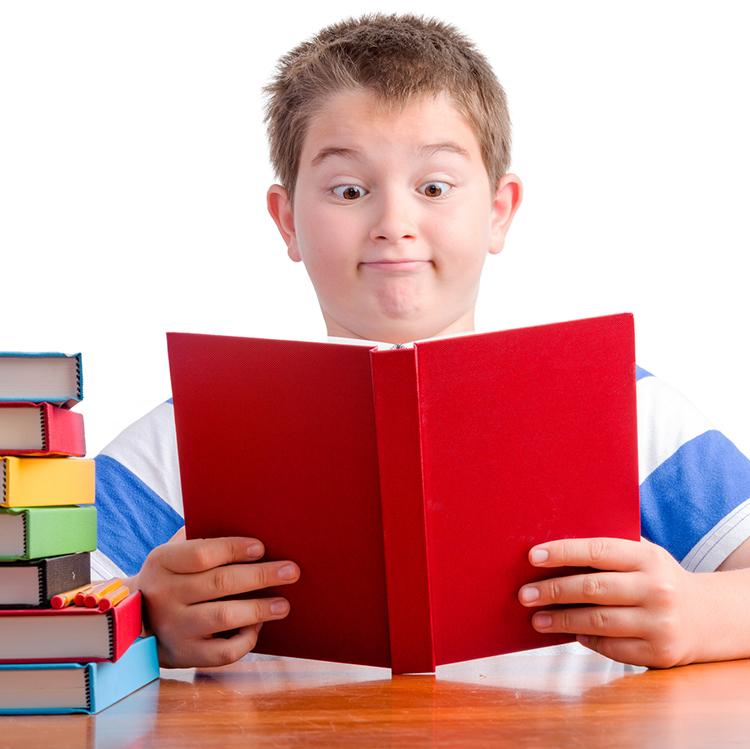 Surprised schoolboy reading book