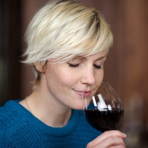 closeup portrait of young blond woman drinking red wine